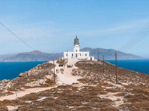 la spettacolare immagine del faro con alle spalle l'isola di Tinos